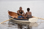 African couple smiling in row boat